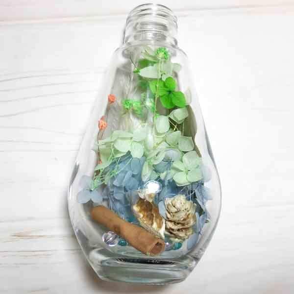 ハーバリウムの作り方-ハーバリウムキットで手作り方法を解説-グリーン色電球型ガラス瓶で花材を全て入れ終わり確認